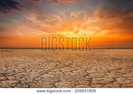 Global worming concept - cracked scorched earth soil drought desert landscape dramatic sunset