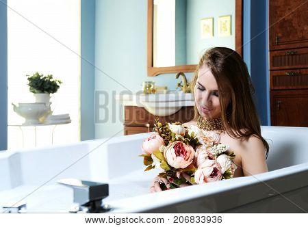 Luxury fashion woman in hotel spa lying in bath tub with bouquet of flowers