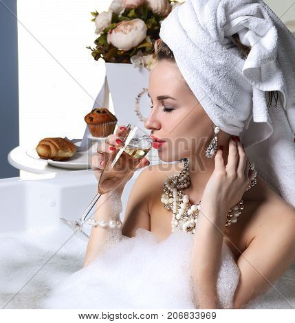 Luxury fashion woman witn soft big towel in the motning take breakfast in hotel spa lying in bath tub drinking glass of champagne