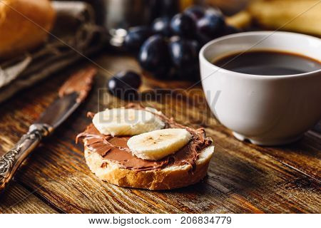 Breakfast with Banana Sandwich with Chocolate Spread Coffee Cup and Grapes.