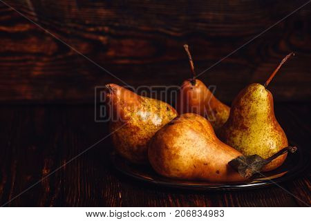 Few golden pears on metal plate over wooden background.