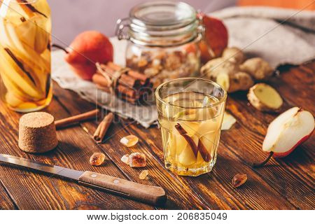 Glass of Water Infused with Sliced Pear Cinnamon Stick Ginger Root and Some Sugar. Ingredients Scattered on Wooden Table.