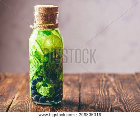 Bottle of Infused Water with Lime Mint and Blueberry. Copy Space on the Right.