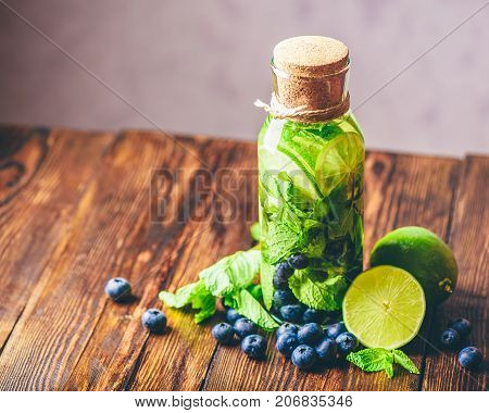 Bottle of Detox Water Infused with Lime Mint and Blueberry and Ingredients on Table. Copy Space on the Left. High Angle View.