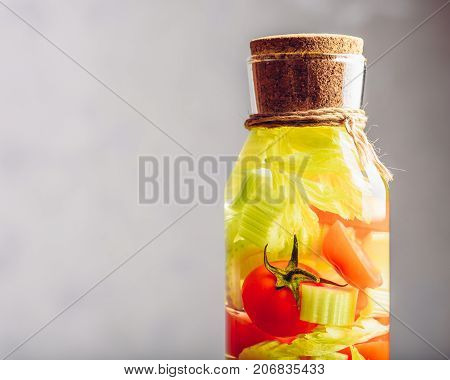 Part of Bottle with Water Infused with Cherry Tomato and Celery Stems. Copy Space on the Left.