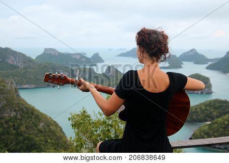 Girl playing acustic guitar on the top of the mountain. The view point of Ang thong island.Thailand