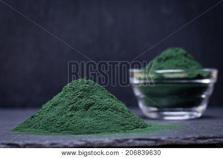 Organic Spirulina Algae Powder On Black Slate Platter Background