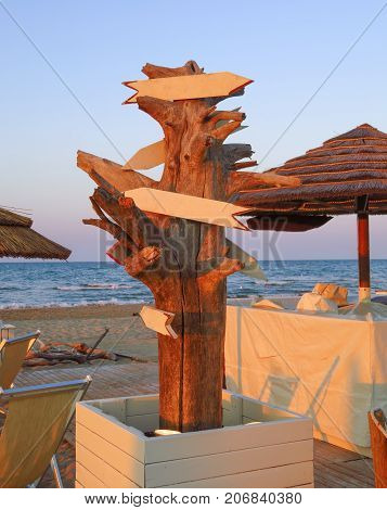 Wooden empty direction signpost with arrows on the beach