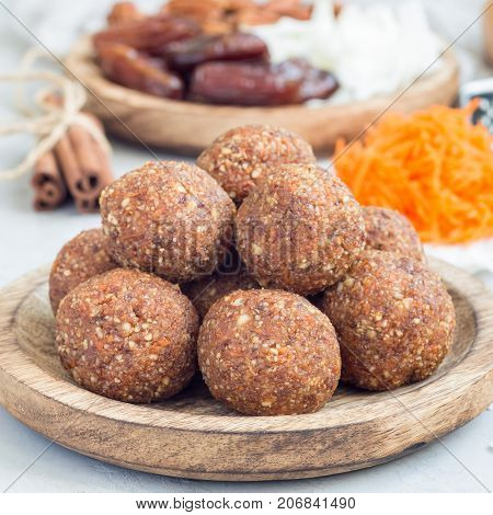 Healthy homemade paleo energy balls with carrot nuts dates and coconut flakes on wooden plate square format