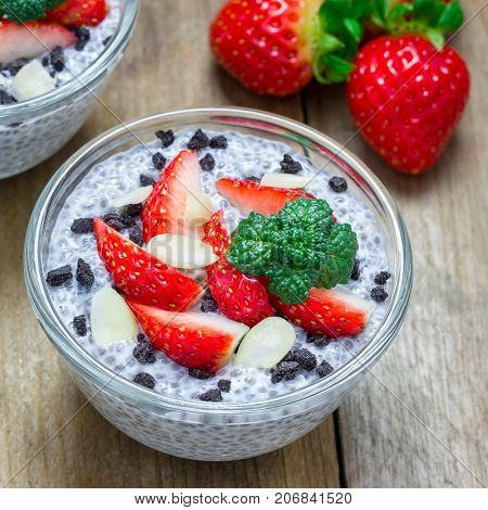 Chia seed pudding with strawberries almond and chocolate cookie crumbs on a wooden table square format