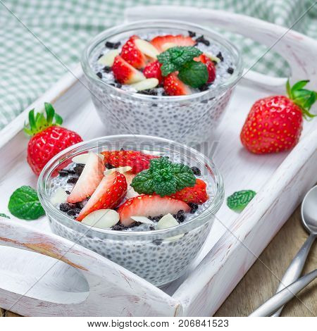 Chia seed pudding with strawberries almond and chocolate cookie crumbs in a wooden tray square format
