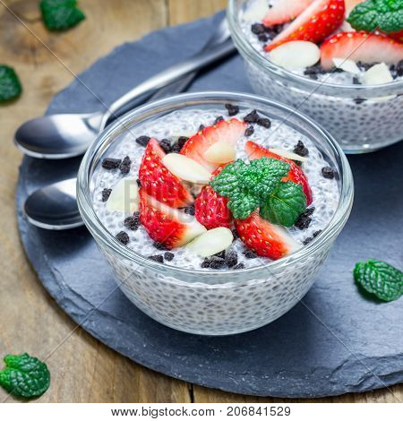 Chia seed pudding with strawberries almond and chocolate cookie crumbs on a slate board square format