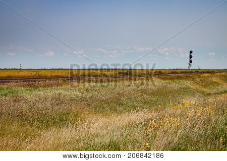 Railroad Track on Canadian Prairie in Late Summer Under Blue Sky