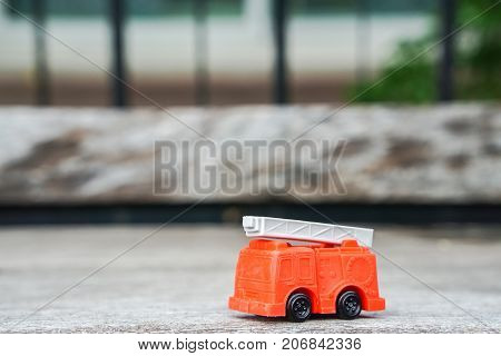 red electricity and utility service truck model toy on wooden floor for kid