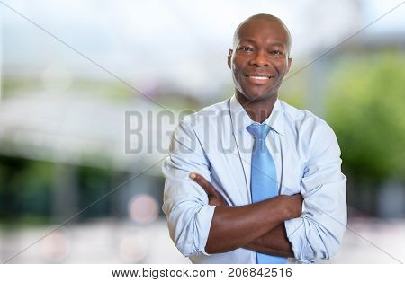 Laughing african american businessman with tie outdoor in summer