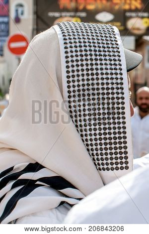 Orthodox hassidic Jew pray in a holiday robe and tallith.