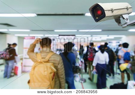 CCTV security indoor camera system operating in airport with people queue at immigration control background people transportation surveillance security and safety technology concept