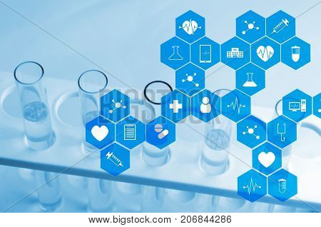 close up chemical liquid in laboratory test tube with medical icon in hexagon pattern blue color tone laboratory science chemical and medical research concept soft and selective focus
