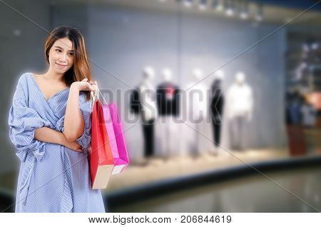 young asian woman happy smiling with shopping bags while standing at showcases fashion brand name clothes display in department store shopping mall sale people payment and shopping online concept