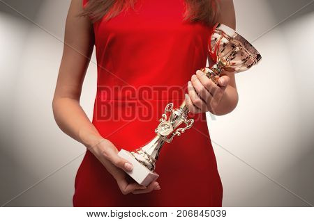 Winner. First place. Young woman in red dress holding in hands golden cup. Award ceremony. VIP client. Success.