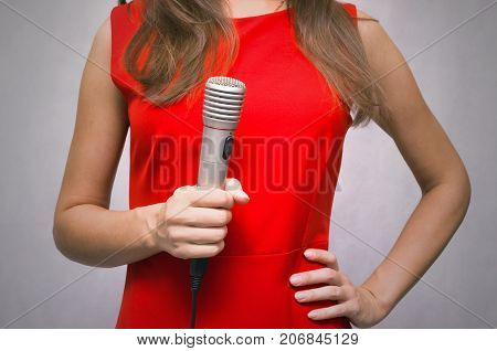 Reporter. Newscaster. Presenter. Young woman in red dress holding in hands microphone.