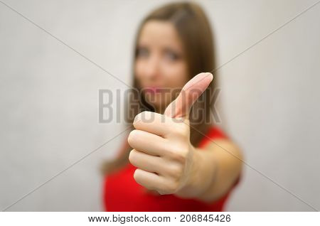 Young smiling woman in red dress showing Thumbs up sign by her hand. Success. Approving gesture. Confirmation.