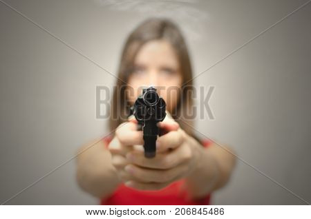 Young woman in red dress aiming and shooting with revolver gun in the screen. Dangerous girl.