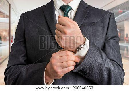 Businessman Fixing His Cufflinks In Shopping Center