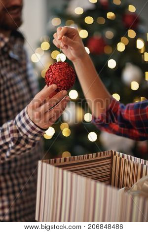 Couple in love decorating Christmas tree, close up