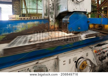 Work of an industrial surface grinding machine. Grinding of a flat metal part. Sparks fly out from under the grinding wheel. Grinding with a coolant. poster