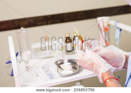 Doctor with syringe in hand. Medical health professional holding a vaccine injection. Concept of vaccination against flu and Viral Diseases