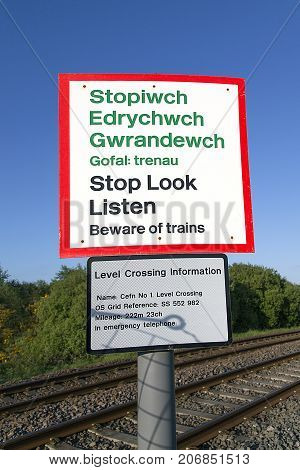Swansea, UK: May 04, 2017: Warning sign on a railway pedestrian crossing. Arriva Trains Wales is a British train operating company operating the Wales & Borders franchise.