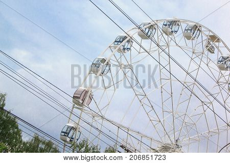 Large ferris wheel is spinning in an amusement park. Fairground ride.