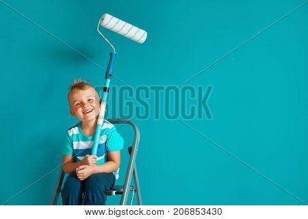 The Child Paints The Blue Wall With A Roller. The Boy Holds A Large Brush For Painting. Home Repairs