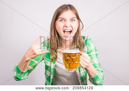Portrait an euphoric sports fan holding a beer bottle. Woman with beer.