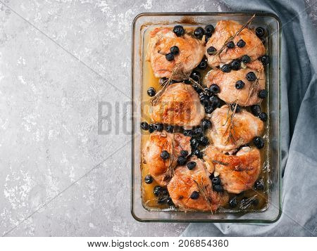 Corsican chicken thighs with rosemary, black olives, garlic in lemon juice and wine. Chicken legs cooked in oven on gray concrete background. Baked chicken leg in heat-proof glass. Top view.Copy space