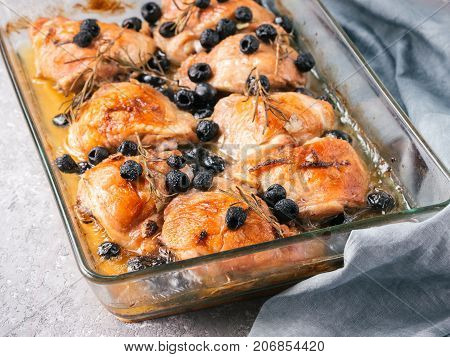 Corsican chicken thighs with rosemary, black olives, garlic in lemon juice and wine. Chicken legs cooked in oven on gray concrete background. Baked chicken leg in heat-proof glass. Copy space