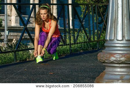 Young Fit Woman In Rome, Italy Tying Shoelaces