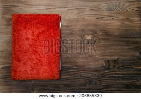 Old red book on wooden table background. Education.