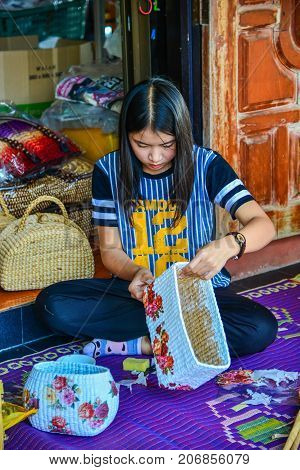 Phayao Thailand - February 15 2014: Woman attaching flower sticker to wicker handbag made from papyrus in Phayao Thailand
