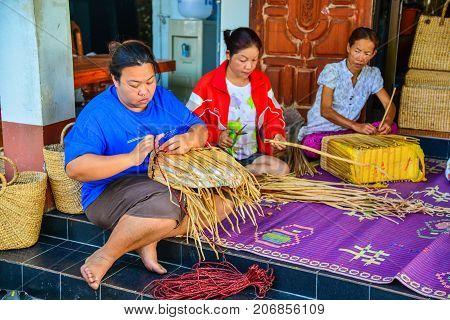 Phayao Thailand - February 15 2014: Women weaving wicker handbag made from papyrus in Phayao Thailand
