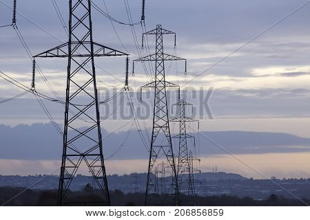 Electrical pylons at sunset leading to a populated area  to provide the necessary power,