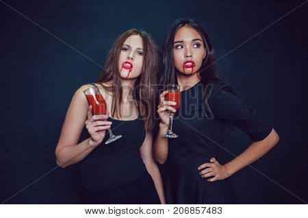 Attractive girls in the image of vampires hold glasses with blood. Halloween.