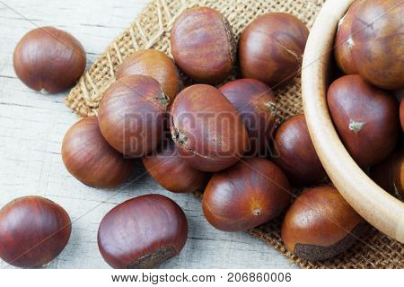 Roasted chestnuts on sackcloth and wooden floor.