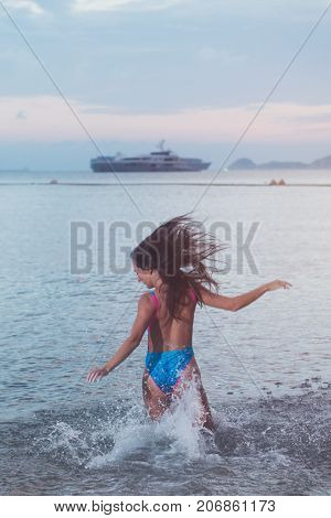 Back view of carefree young woman with her hair streamed running into sea splashing water at sunset with a ship on horizon