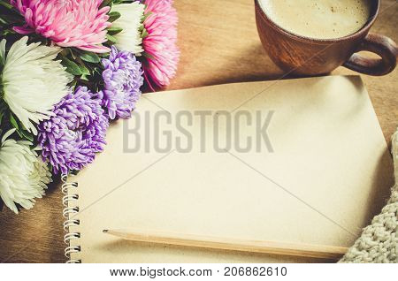 Flat lay of blank brown notebook with autumn flowers and cup of coffee on wooden table. Copy space.