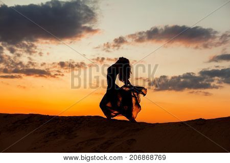 Female figure during a dance against the backdrop of the setting sun.