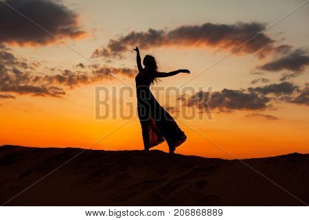 Female figure against the backdrop of the setting sun.