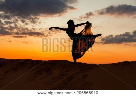 Dancing woman figure on the background of the setting sun.