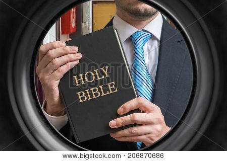 Jehovah witness is showing bible behind door. View from peephole.